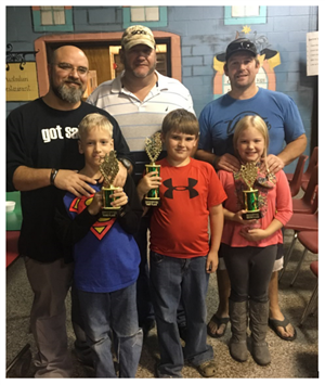 Children holding trophies with their dads.