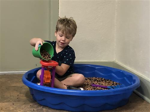 boy pouring beans in a toy